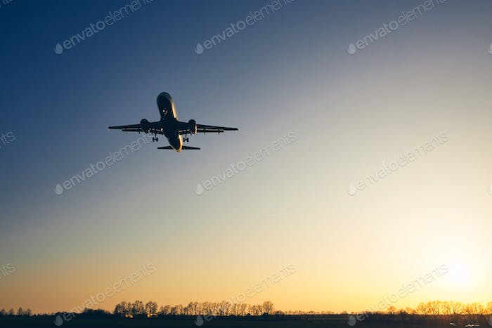 Airplane landing at golden sunset