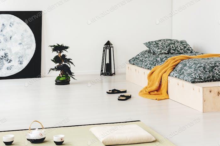 Orange blanket on wooden bed in bedroom interior with moon poste