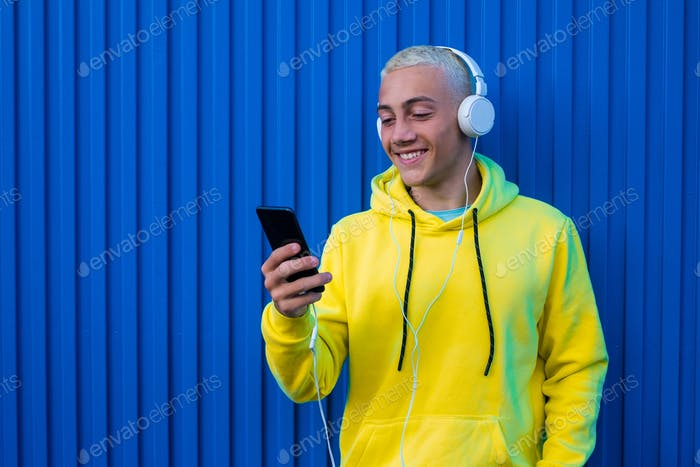 one young man hearing and listening music smiling and looking at the phone having fun