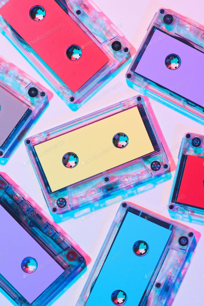 top view of arranged colorful audio cassettes on purple background