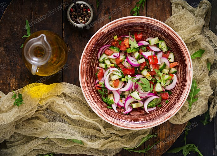 Tomato, cucumber and red onion salad with black pepper and arugula