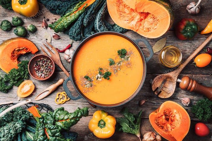 Pumpkin soup with vegetarian cooking ingredients, wooden spoons, kitchen utensils on wooden
