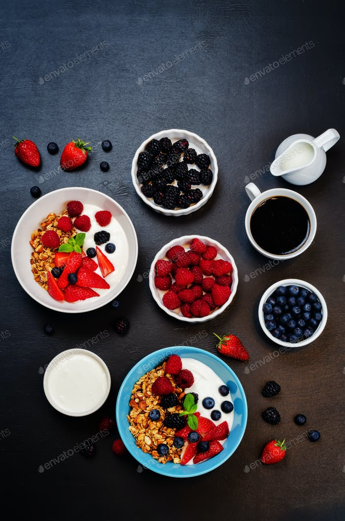 Healthy breakfast with granola, greek yogurt, berries and milk