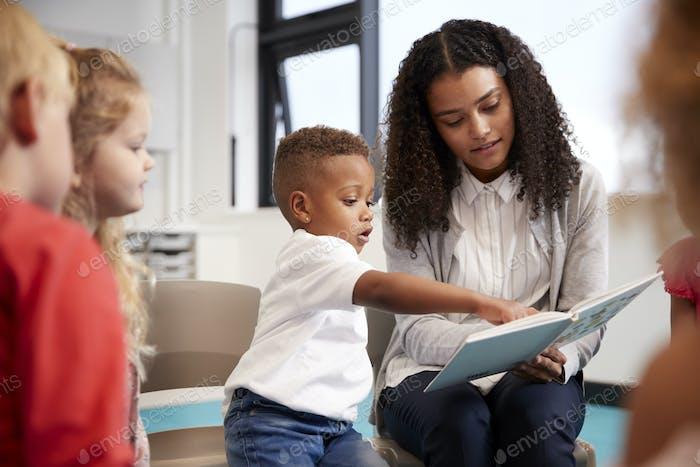 Säuglings-Schuljunge zeigt in einem Buch von der Lehrerin gehalten