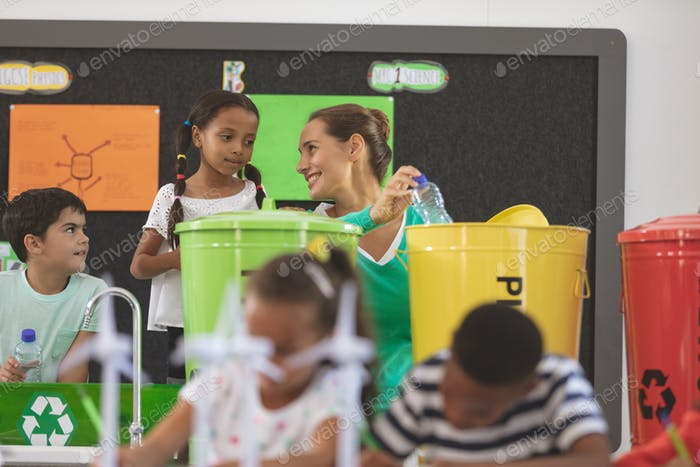 Vorderansicht des Lehrers diskutiert Schulkinder über grüne Energie im Klassenzimmer