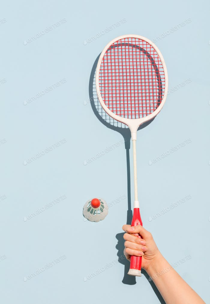 Woman's hand holding a retro badminton racket