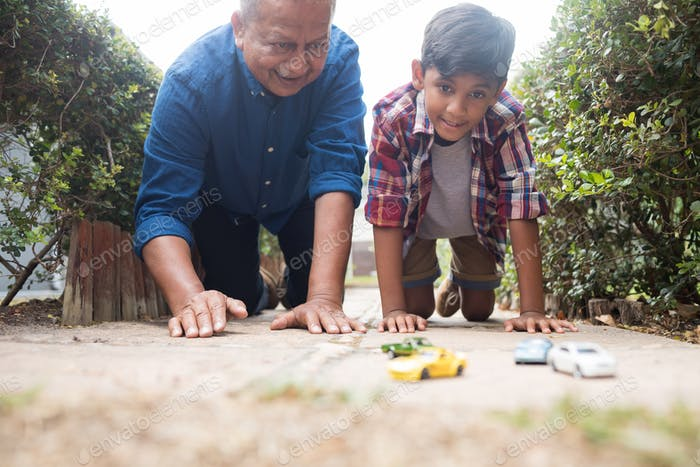 Boy and grandfather playing with toy cars
