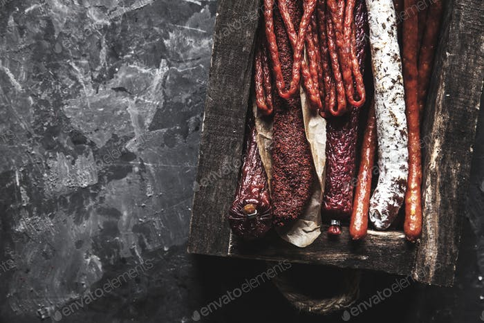 Salami with spices in an old tray. On a dark gray background