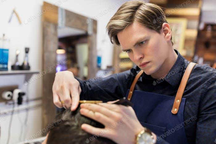 Mann und Friseur schneiden Haare im Friseurladen