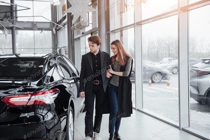 Ich mag dieses Auto. Schönes junges Paar stehen beim Händler die Wahl des Autos zu kaufen