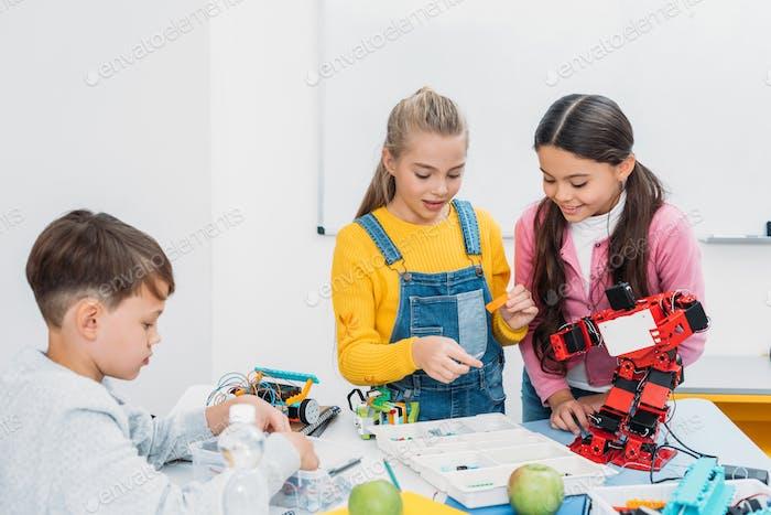 schoolchildren programming robot together during STEM educational class