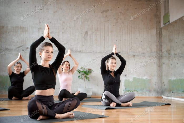 Group of women doing yoga in hall