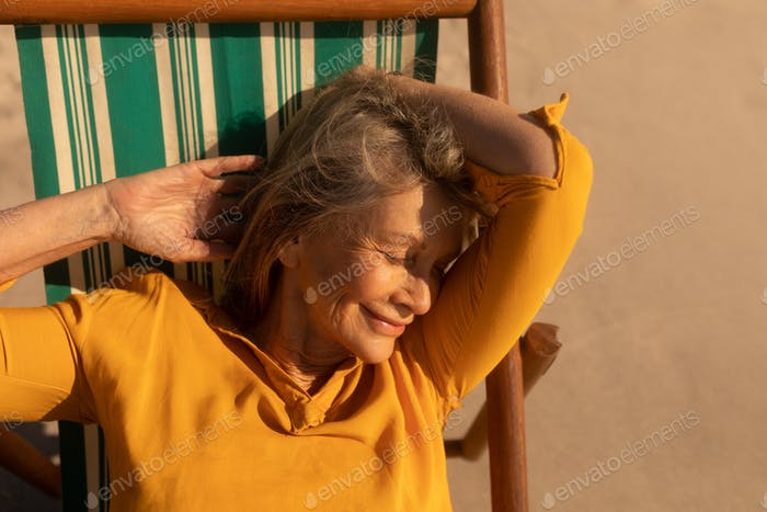 Front view of active senior woman sleeping on sun lounger at beach