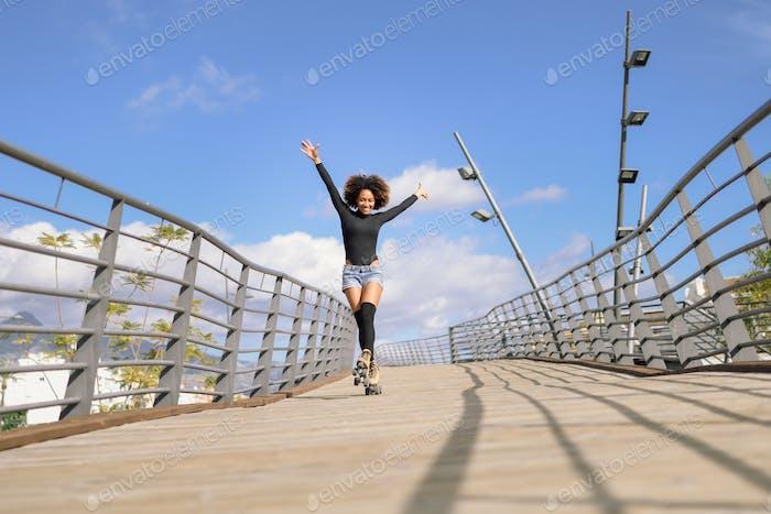 Afro Frisur Frau auf Rollschuhe Reiten im Freien auf städtischen Brücke