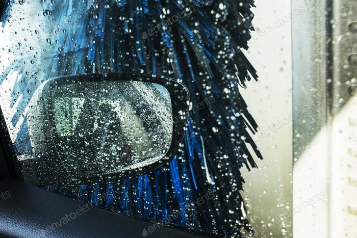 View from the inside of a car in an automated car wash, blue washers and soapy water over the