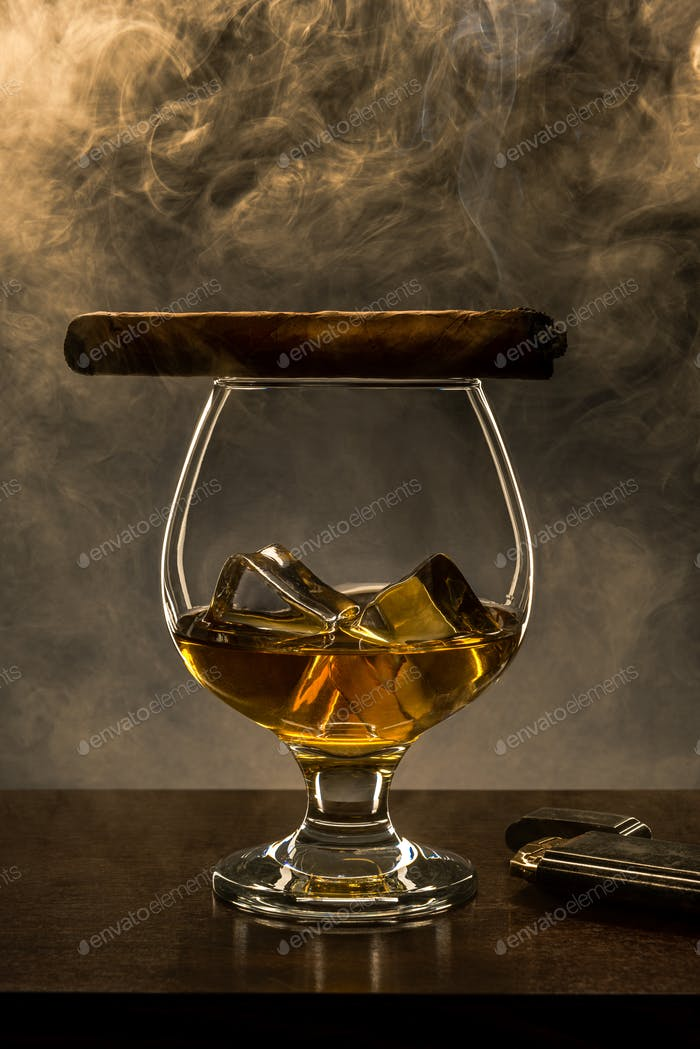 Smoking Cuban Cigar on Top of Elegant Whisky Glass with Ice Cubes. Copy Space Background