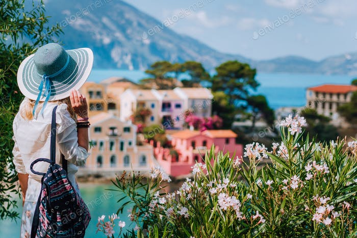 Blond beautiful woman in blue sun hat and white clothes enjoying view of colorful tranquil village