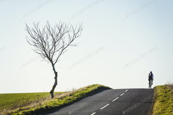 A cyclist riding along a country road on a clear sunny winter day, on the brow of a hill.