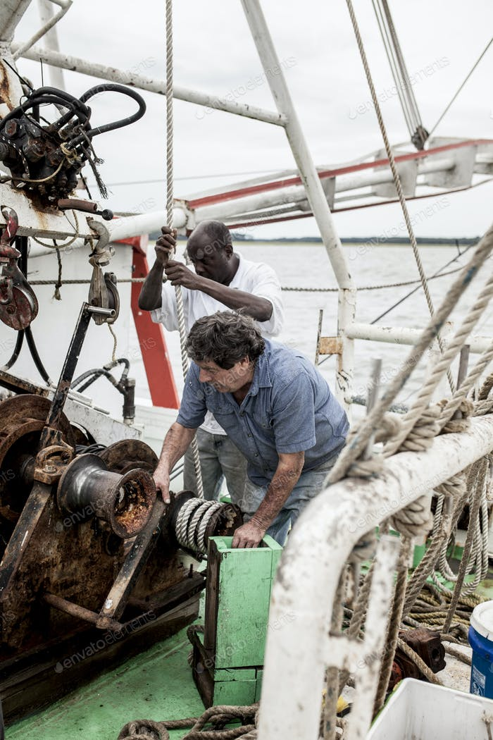 Commercial fishermen working on the deck of a shrimp boat