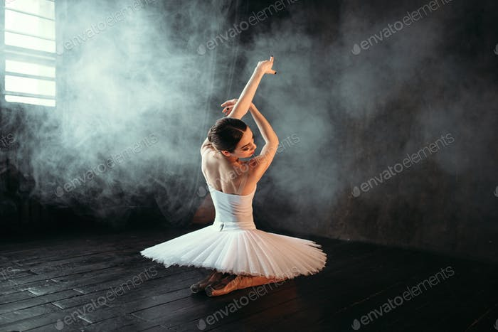 Female classical ballet performer sitting on floor
