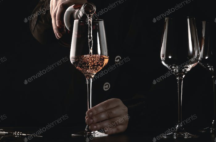 Sommelier pouring rose wine into glass at wine tasting