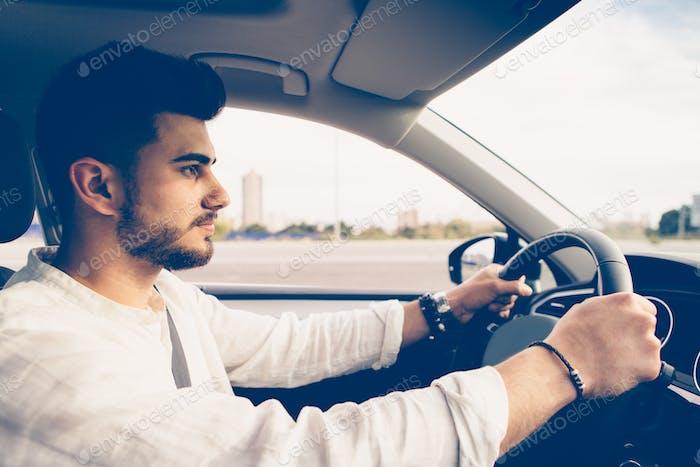 Young man drives a car
