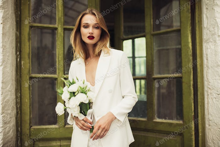 Young gorgeous woman in white jacket and dress holding little bo