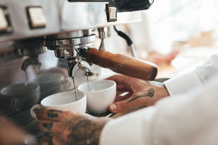 Close up barista hands making coffee by coffee machine in restaurant