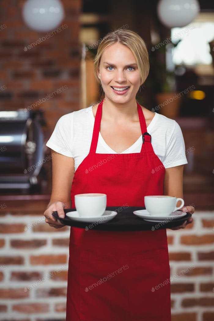 Portrait of a waitress holding a tray with coffees at the coffee shop