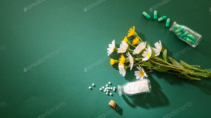 Homeopathy, globules and pills on green background