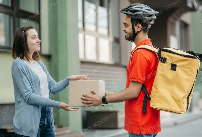Happy woman receives parcel. Deliveryman in helmet with yellow backpack gives box to client, near