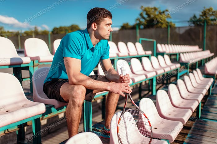 Man with tennis racket sitting on the podium