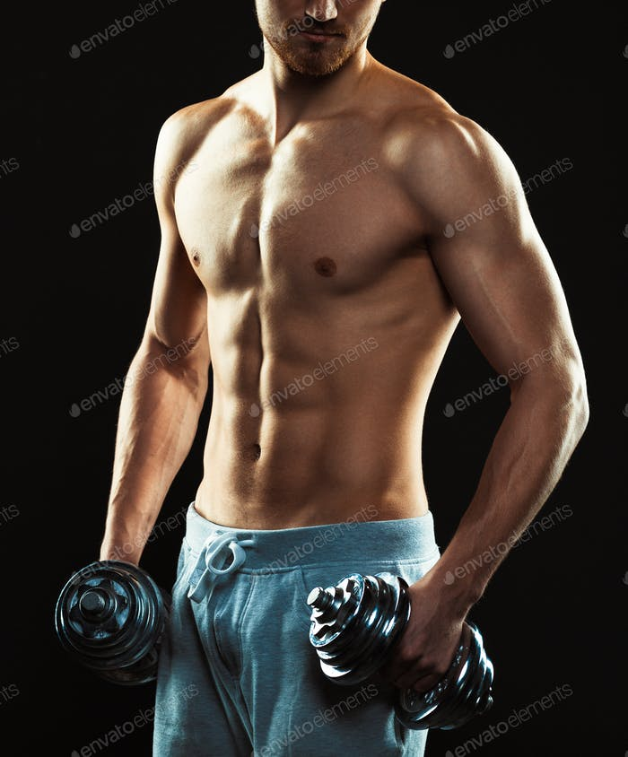 Athletic attractive man with dumbbells on the black