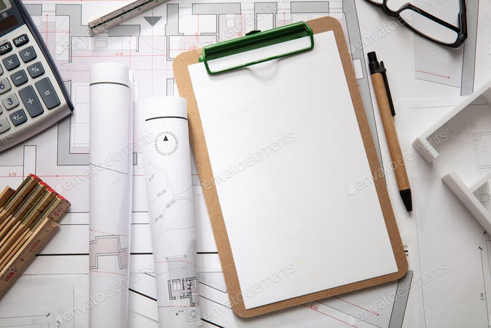 Construction concept. Residential building blueprint drawings and office supplies