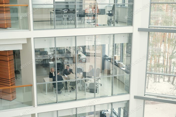 People working behind glass wall in office lobby