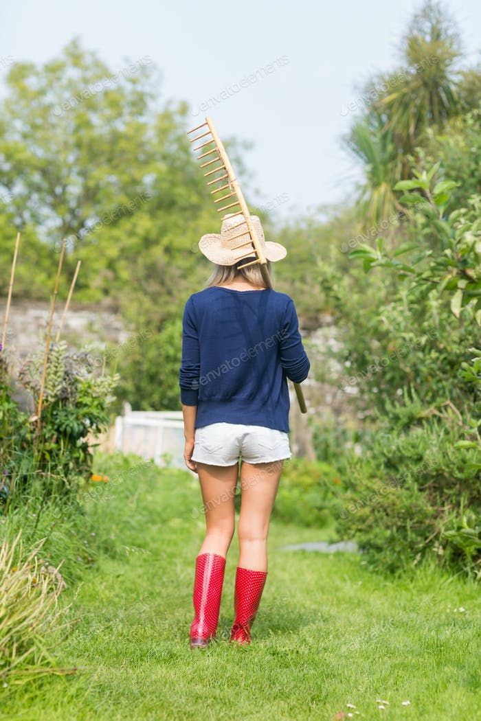 Gardening blonde holding a rake at home in the garden
