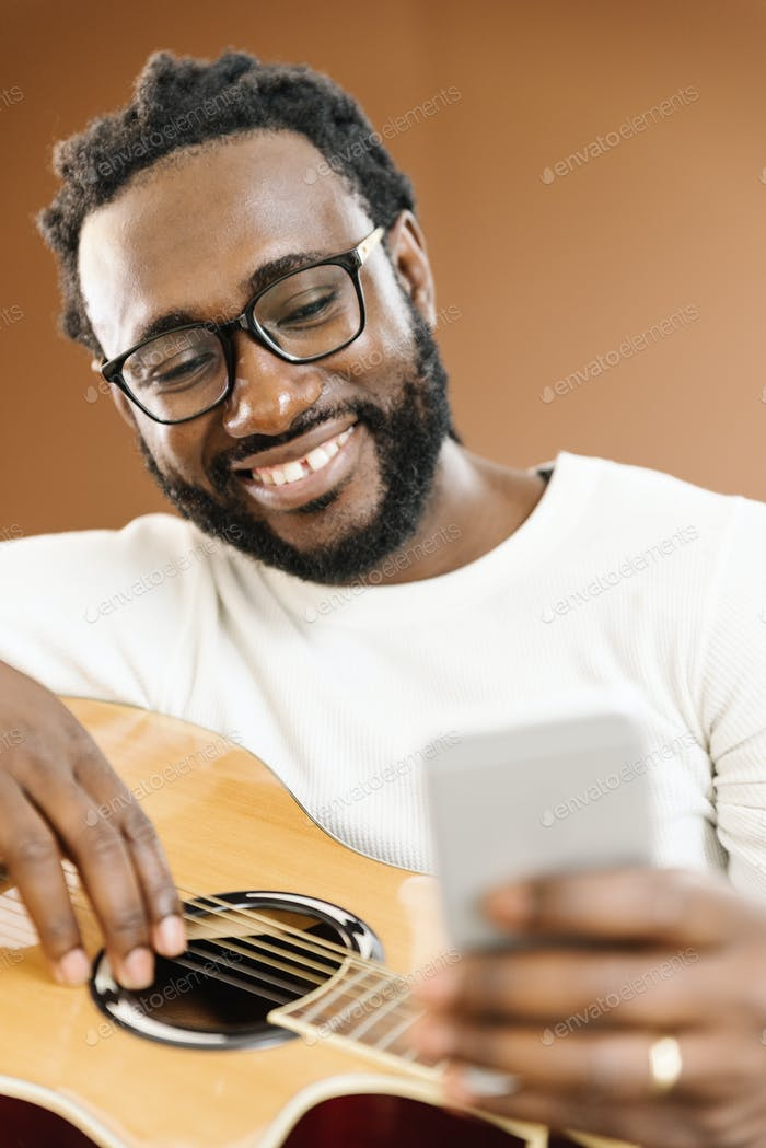 Guitarist with guitar using mobile.