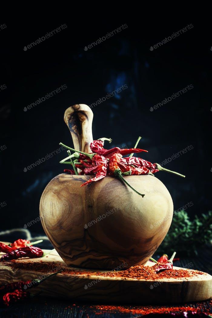 Trockener roter Chilischote in einem Mörser und Stößel, dunkler Hintergrund, selektiver Fokus