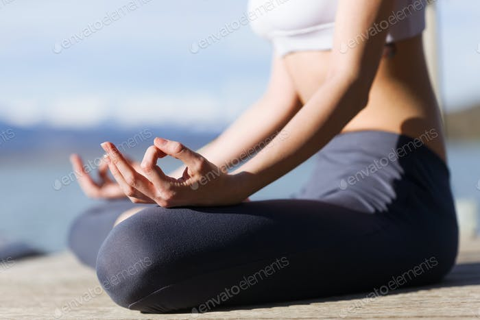 Close-up of young woman doing yoga next to the lake.