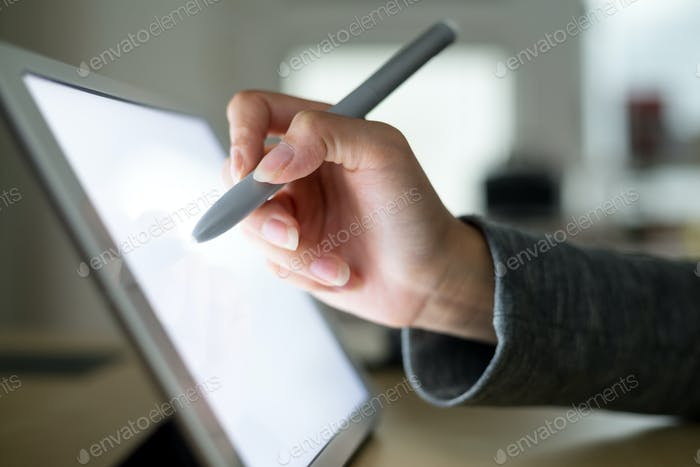 Woman drawing on tablet with pen