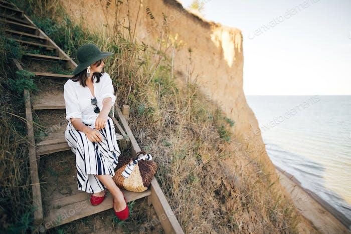 Boho Mädchen im Hut sitzen auf Holztreppen in sonnigem Licht auf sandigen Klippen in der Nähe von Meer