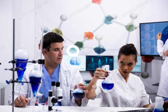 Female scientist in white coat holding a test tube with blue solution
