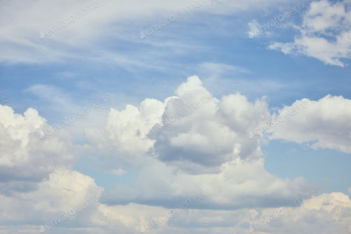 Peaceful cloudscape with white clouds on blue sky