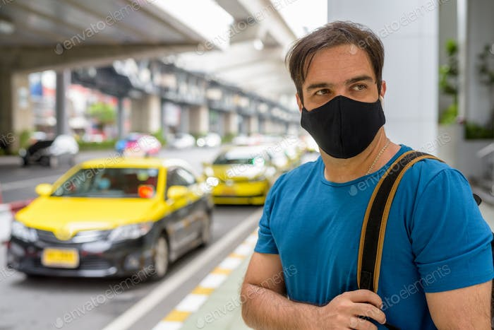 Portrait of Persian man with mask thinking at the taxi station