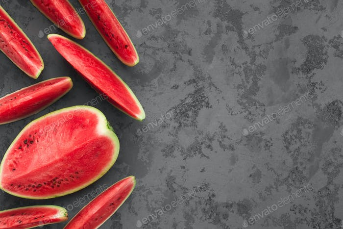 Ripe red cut watermelon on grey concrete background