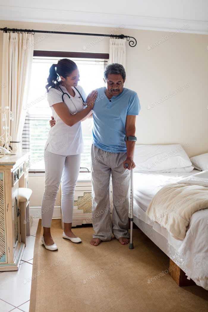 Thumbnail for Female doctor helping senior man to walk with walker in bedroom