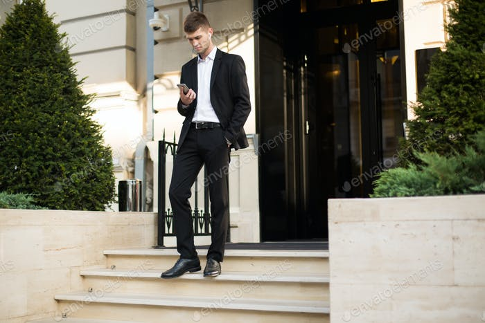 Young attractive businessman in black suit and white shirt with