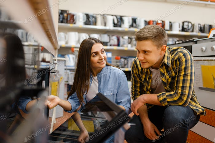 Couple choosing electric oven in electronics store