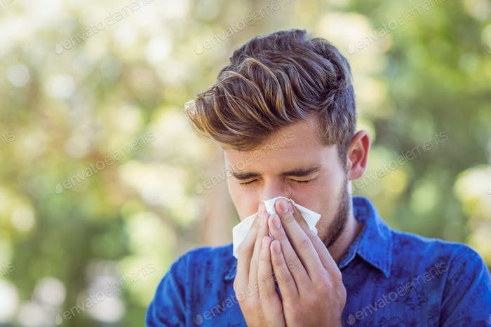 Handsome hipster blowing his nose on a sunny day