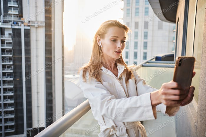 Beautiful girl with earphones thoughtfully taking selfie on balcony with beautiful skyscrapers view